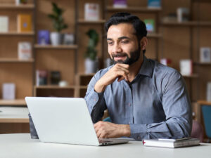 Smiling bearded real estate lawyer remote working on laptop in home office