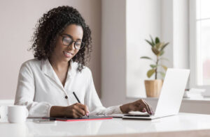 Smiling female real estate lawyer working remotely on laptop
